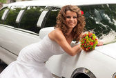 Bride with original bouquet leaning on a white car — Stock Photo