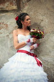 Bride with wedding bouquet leaning against the wall (profile) — Stock Photo