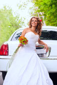 Bride with original bouquet near the white car — Stock Photo
