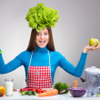 Funny portrait of a woman with the salad on her head — Stock Photo