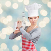 Woman in chef's hat firing a gun with the mixer — Stock Photo