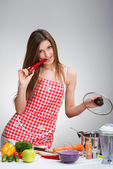 Cooking woman biting the red pepper, gray background — Stock Photo