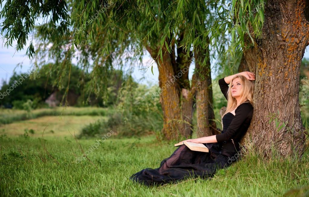 Triste femme assise sous un arbre photo 32598043 for Arboles que dan sombra para jardin
