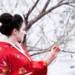 Geisha looking at a little red flower — Stock Photo