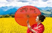Kırmızı şemsiye ile bir kadın portresi asya tarzı — Stok fotoğraf