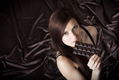 Portrait of pretty young woman nibbling the bar of chocolate — Stock Photo