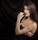 соблазнительная молодая женщина, кусаться шоколадные конфеты — Стоковое фото