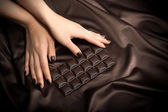 Female hands touching the dark chocolate bar — Stock Photo