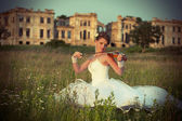 Bride with violin in front of ruins — Stock Photo