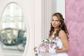 Bride with wedding fan-bouquet before a mirror — Stock Photo
