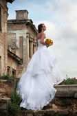 Bride in front of ruins, in profile — Stock Photo