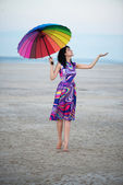 Barefooted woman with colorful umbrella — Stock Photo