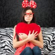 Sad girl with a heart cushion — Stock Photo