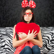 Stock Photo: Sad girl with a heart cushion