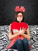 Sad girl with a heart cushion — Stock Photo