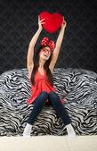 Funny happy girl with a heart cushion — Stock Photo