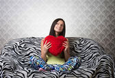 Portrait of a girl with a red heart cushion — Stock Photo