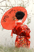 Geisha with red umbrella at the riverside (back view) — Photo
