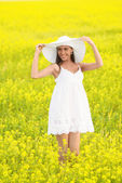 Portrait of smiling pretty girl in white in blooming field — Stock Photo