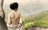 Woman with snake tattoo on her back on the tree branch — Stock Photo