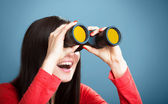 Girl looking through the binoculars — Stock Photo