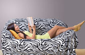 Girl reading a book at home — Stock Photo