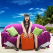 Funny girl with her luggage, tropical beach background — Stock Photo