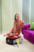 Girl trying to close her suitcase — Stock Photo