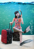 Funny girl with her travel luggage sitting under the sea — Stock Photo