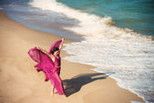 Woman in airy crimson dress on the beach — Stock Photo