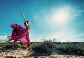 Woman in airy crimson dress running on sand beach — Stock Photo