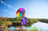 Girl with colorful umbrella at the riverbank — Stock Photo
