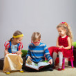 Boy reads a book to little girls — Stock Photo #46417095