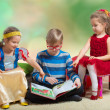 Boy reads a book to little girls — Stock Photo #46417081