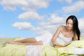 Woman lying in bed and reading the book — Stock Photo