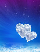 Hearts in clouds against a blue spacу sky — 图库照片
