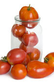 Red tomatoes in a glass jar — Stock Photo