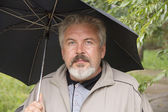 Looking man of fifty years with an umbrella — Stock Photo