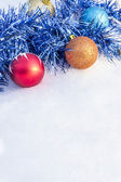 Christmas ornaments lying in the snow — Stockfoto