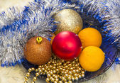 Tangerines and Christmas tree ornaments on a blue plate — Stock Photo