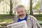 A middle aged man reading a newspaper in a park — Stock Photo