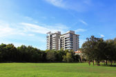 Apartment building with grass and sky — Stock Photo