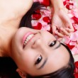 Girl smiling close-up with rose background — Stock Photo #14030190