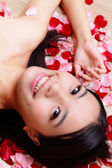 Girl smiling close-up with rose background — Stock Photo