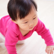 Crawling baby girl on living room floor — Stock Photo
