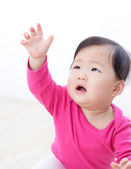 Girl baby looking up and rise her arm — Stock Photo