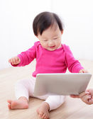 Girl baby happy watch tablet PC — Stock Photo