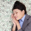Business woman sleeping on money bed — Stock Photo
