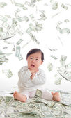 Baby surprised funny face with money rain — Stock Photo