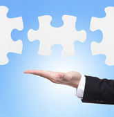 Business man showing puzzle — Stock Photo